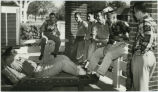 Beta Theta Pi students relaxing on porch outside fraternity house