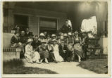Omega Phi Fraternity members and their dates on porch