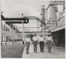 [Everette DeGolyer, Sr. walking through an industrial factory with Senator Antonio J. Bermudez,...