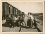 [German officers conversing with women and child in rail yard]