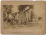 [People in front of house with attached log cabin, one of the original houses in Seguin, Texas]