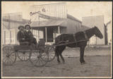 [Two men in carriage with photograph gallery in background, Uvalde, Texas]