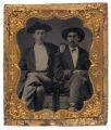 [Two men, seated in wooden chairs]