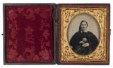 [Woman holding cased image of three men]