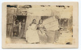 [Two women seated near children in doorway of house]