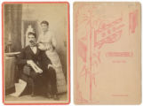 [Couple, man seated, woman standing]