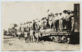 [Group of soldiers with supplies on a railroad flatcar]