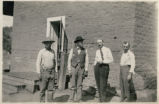 [Four company employees outside adobe building, Cananea, Mexico]