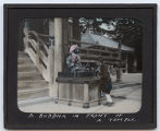 Lantern slide 'A Buddha in front of a Temple'
