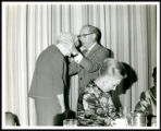 Photograph of Kate Warnick receiving a blessing from Rabbi Levi A. Olan during a luncheon on...