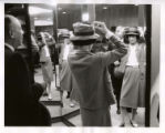 [Coco Chanel Trying on a Hat While Touring the Neiman Marcus Store with Stanley Marcus]