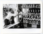 [Man tossing ball in game booth at the midway, State Fair of Texas]