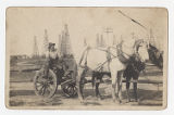 [Man sitting in wagon with mules in oil field]